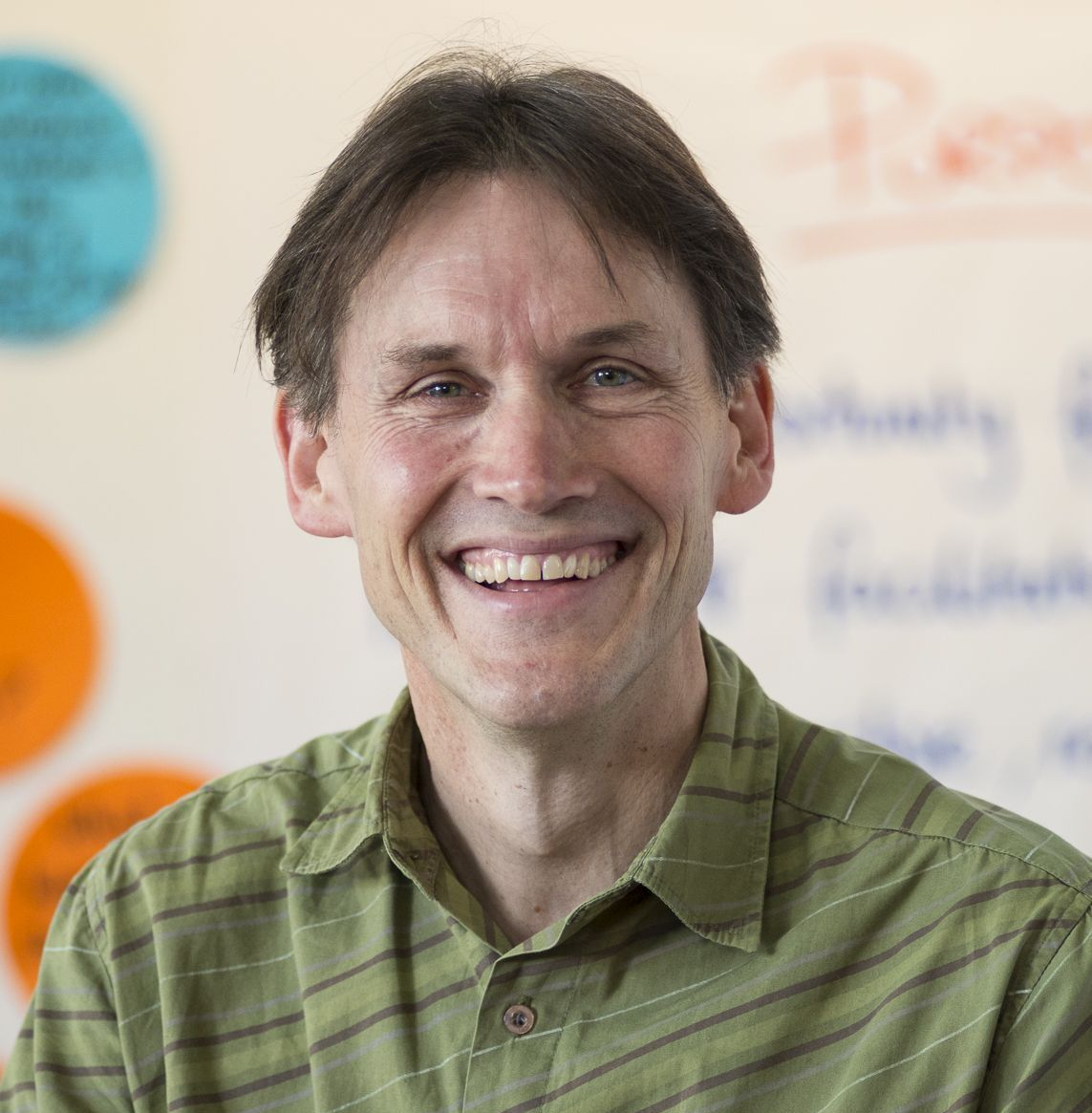 Smiling man in his 50s in a work shirt with no tie, head and shoulders only, whiteboard/workshop background
