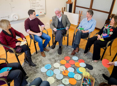 Five adults (women and men) in casual professional work clothes seated as part of a circle looking at one of the people speaking. They are in a workshop setting with paper circles with notes on the floor in front of them